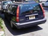 A navy blue Volvo station wagon 850, with New Jersey plates, parked on a city street