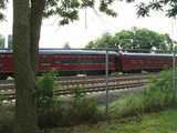 A historic train, painted red, reading: NORFOLK SOUTHERN, behind a chain-link fence on a bright, cloudy day