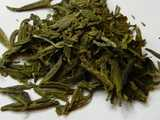 Flat green tea leaves, with a rich golden-yellowish green color