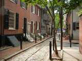A tiny cobblestone alley with brick streets, with old brick rowhouses, and a paved side-street going to the right
