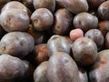 Whole, large, purple potatos, with one small red potato mixed in