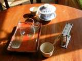 A lidded bowl with Chinese characters, hourglass tea timer, small glass jar on a plate, and two small teacups