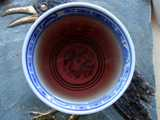Small chinese teacup with brownish / reddish / purplish herbal infusion in it, on a hotplate