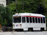 A SEPTA Trolley, white with the red and blue SEPTA logo, showing overhead wires and trees in the background, with the marquee reading: 13 58th-CHESTER