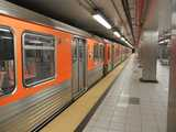 An orange subway train in a newish, mostly gray and silver subway station