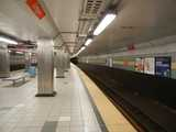 Interior of a subway station, clean, relatively new, with gray tile and orange signs reading: Oregon