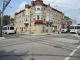 A city intersection with an attractive 3-story building with a turret, with a crossroads of trolley tracks in the street, and two trolleys right and left, one on each street