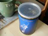 A blue canister with a clear plastic lid, containing loose tea, and a mug labelled tea, on a desk, with a chair