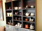 A shelf with teapots, tea cups, and tea sets, in various styles and from various cultures