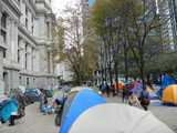 Rows of colorful tents on a plaza, with Philadelphia's city hall on the left, and some mostly bare trees in the background, with tall buildings behind them