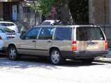 A beige Volvo stationwagon 940 turbo, in good condition, parked on a city street