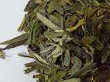 Loose-leaf dragonwell green tea, with long, flat leaves, this one showing blunt ends