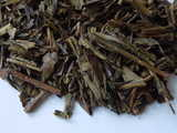 Closeup of roasted green tea leaves, showing dark brown, rolled appearance, with some twig