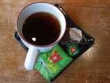 Mug of black tea, with Wissotzky Tea Classic tea bag and wrapper on plate next to mug