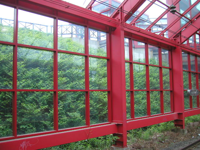 A framework of red metal and glass, with lush green vegetation on a sloping hillside behind