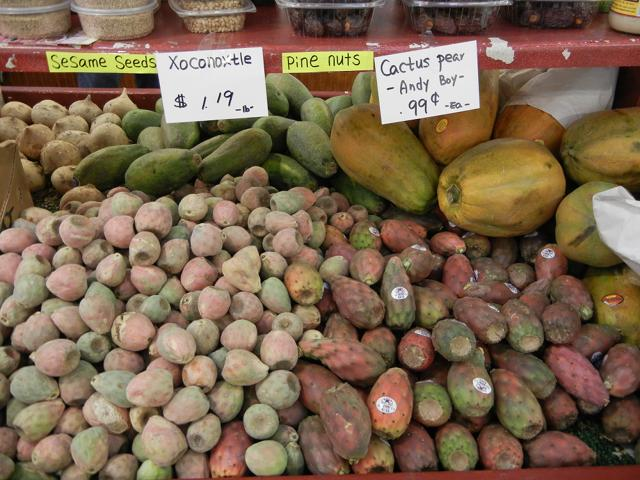 Xoconostle, small cactus pears on the left, pale pink and greenish, and larger, regular cactus pears on the right, rich reddish and deeper green